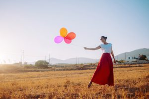 beautiful woman holding colorful balloons in the field